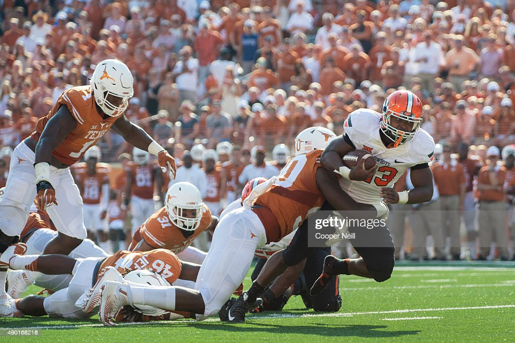 Rennie Childs of the Oklahoma State Cowboys is wrapped up by the Texas Longhorns during the 3rd quarter on September 26 2015 at Darrell K RoyalTexas...