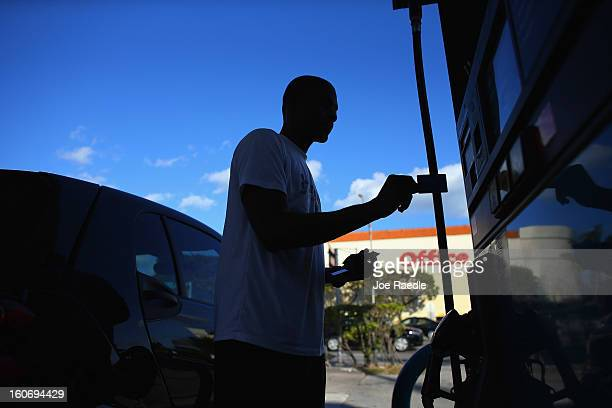 Rennie Valius uses a gas station's pump to fill his vehicle with gas on February 4 2013 in Miami Florida Reports indicate that gas pump prices are at...