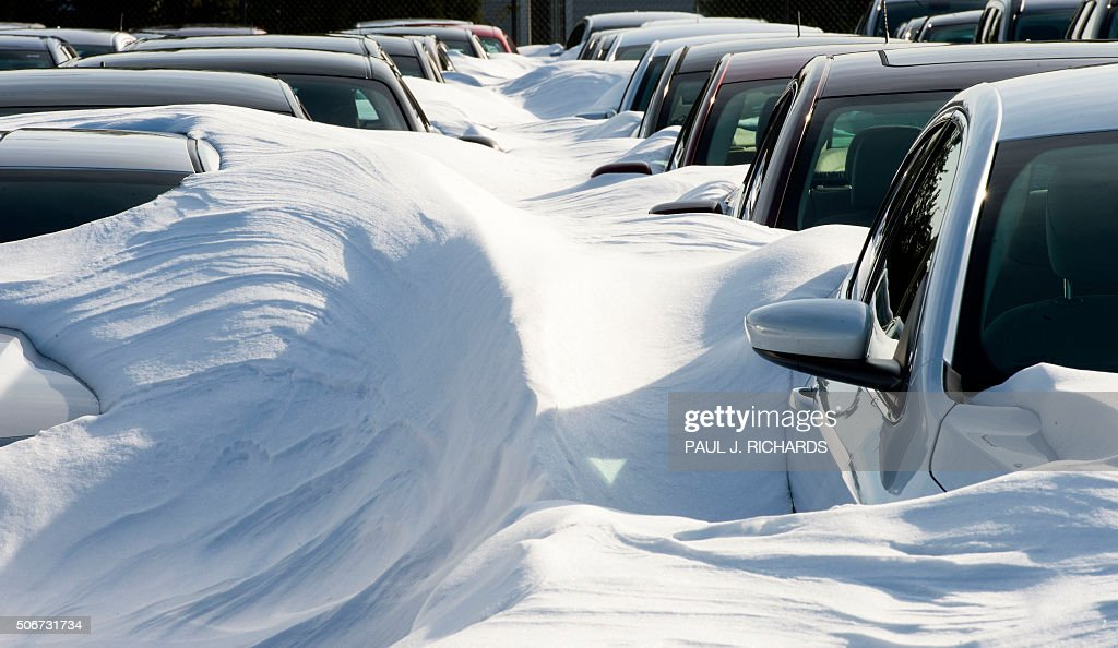 Rental cars are buried in snow at Dulles International Airport January 25 outside Washington DC in SterlingVirginia The icy streets of the US capital...