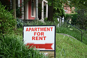 Apartment for rent sign displayed on residential street. Shows demand for housing, rental market, landlord-tenant relations.
