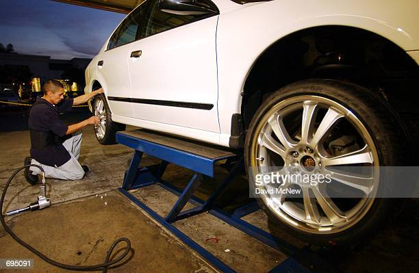 RentAWheel employee Jose Curiel installs 20 inch rental rims on a new Mitsubishi originally equipped with plastic wheel covers January 25 in Santa...