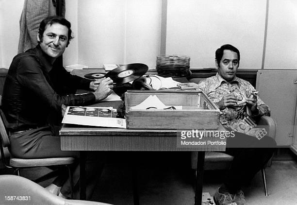 Renzo Arbore and Gianni Boncopagni sitting in a studio choosing records for a radio program Rome Italy 1970