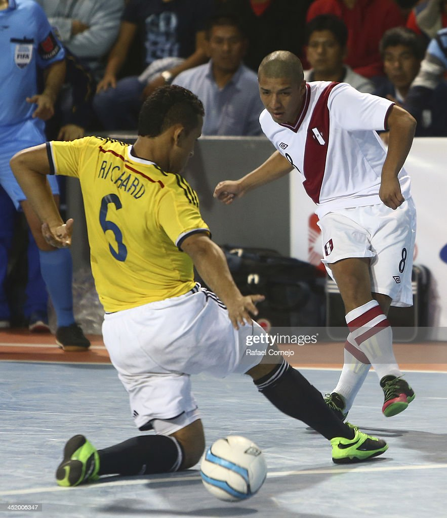 Renzo Ramirez of Peru fights for the ball with Richard Gutierrez of Colombia during a match between Colombia and Peru as part of the XVII Bolivarian Games Trujillo 2013 at Videna San Luis on November 25, 2013 in Lima, Peru.