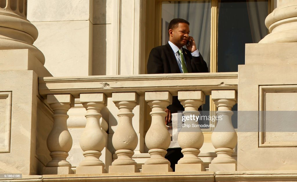 Rep Artur Davis talks on the phone while standing on a balcony outside the US Capitol March 19 2010 in Washington DC Davis who is running for...