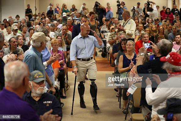 Rep Brian Mast salutes as he arrives for a town hall meeting at the Havert L Fenn Center on February 24 2017 in Fort Pierce Florida Rep Mast held the...