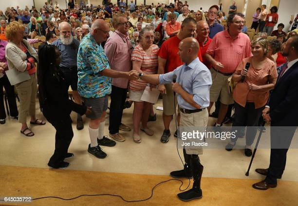Rep Brian Mast shakes hands with Bob Fishel during a town hall meeting at the Havert L Fenn Center on February 24 2017 in Fort Pierce Florida Rep...