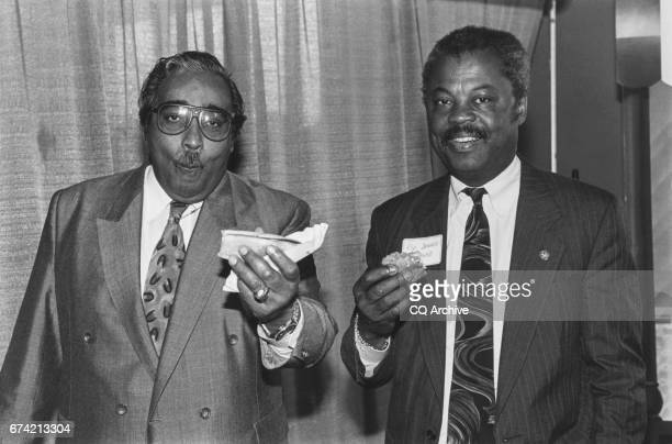 Rep Charles Rangel DNY and Rep Donald M Payne DNJ eats hotdog at Rep Ackerman's Deli Fundraiser on June 8 1992