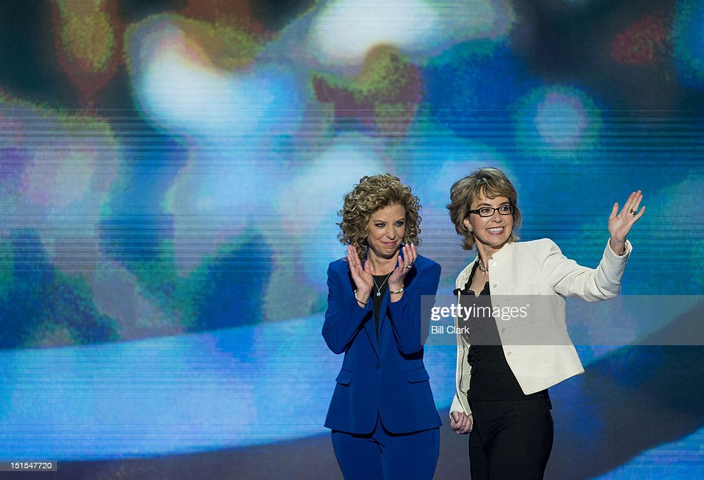 Rep. Debbie Wasserman Schultz, D-Fla., left, escorts former Rep. Gabrielle Giffords, D-Ariz., to the stage to lead the pledge of allegiance at the Democratic National Convention at Time Warner Cable Arena in Charlotte, N.C., on Thursday, Sept. 6, 2012.
