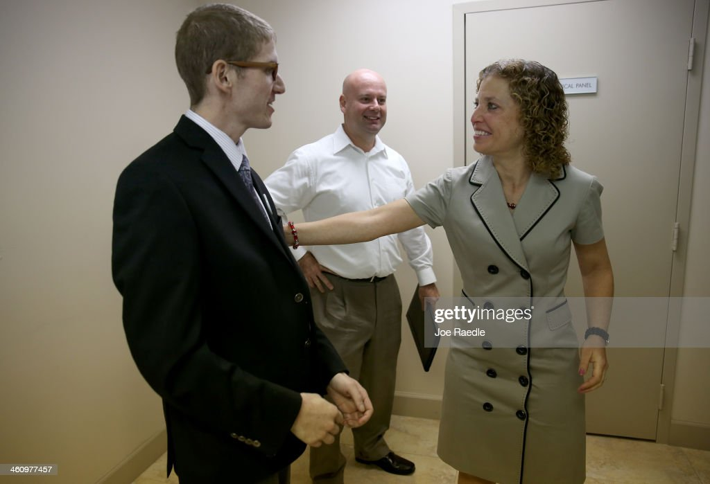 U.S. Rep. <a gi-track='captionPersonalityLinkClicked' href=/galleries/search?phrase=Debbie+Wasserman+Schultz&family=editorial&specificpeople=2528330 ng-click='$event.stopPropagation()'>Debbie Wasserman Schultz</a> (D-FL) (R) speaks with Josh Benson (L) as Martin West looks on during a press conference to speak about the Affordable Care Act during a Hispanic Unity event at Casa Sanjuan Education Centeron January 6, 2014 in Hollywood, Florida. Both Josh and Martin have signed up and now have insurance under the Affordable Care Act.