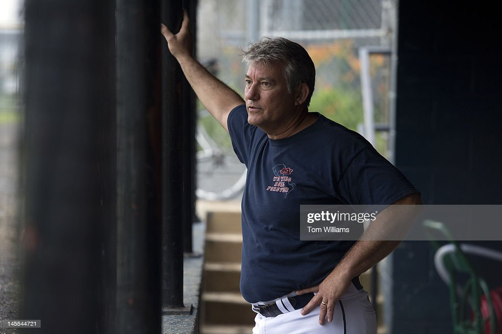 Rep. Dennis Ross, R-Fla., watches republican baseball practice from the dugout at Simpson Stadium in Alexandria, Va.