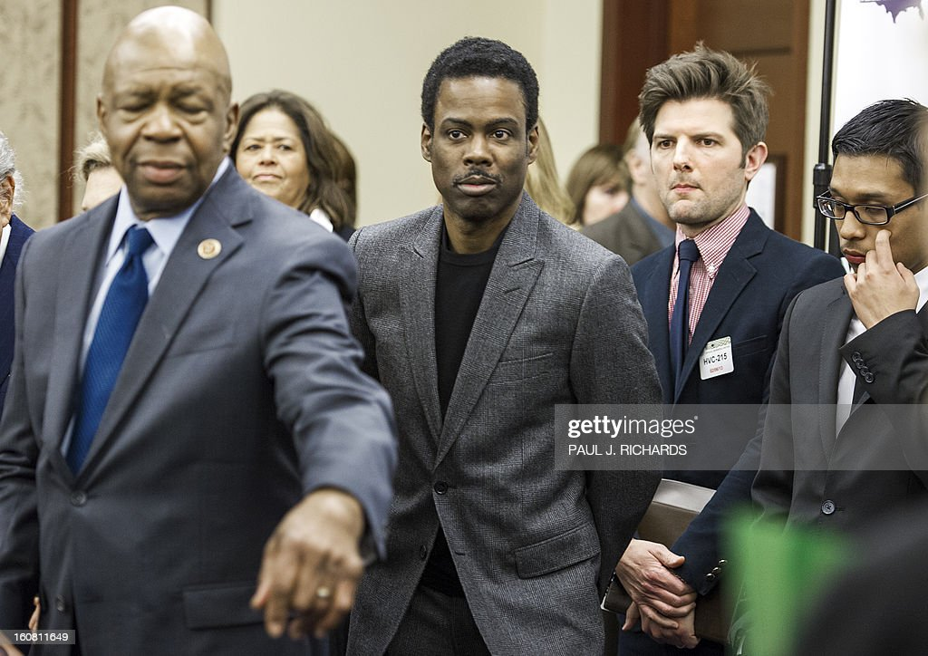 US Rep. Elijah Cummings(L) directs actors Chris Rock(C) and Adam Scott into place at the start of a press conference by Mayors Against Illegal Guns February 6, 2013 on Capitol Hill in Washington, DC. The group of various mayors, victims, entertainers, and political leaders, called for common sense proposals for gun violence prevention. AFP PHOTO/Paul J. Richards