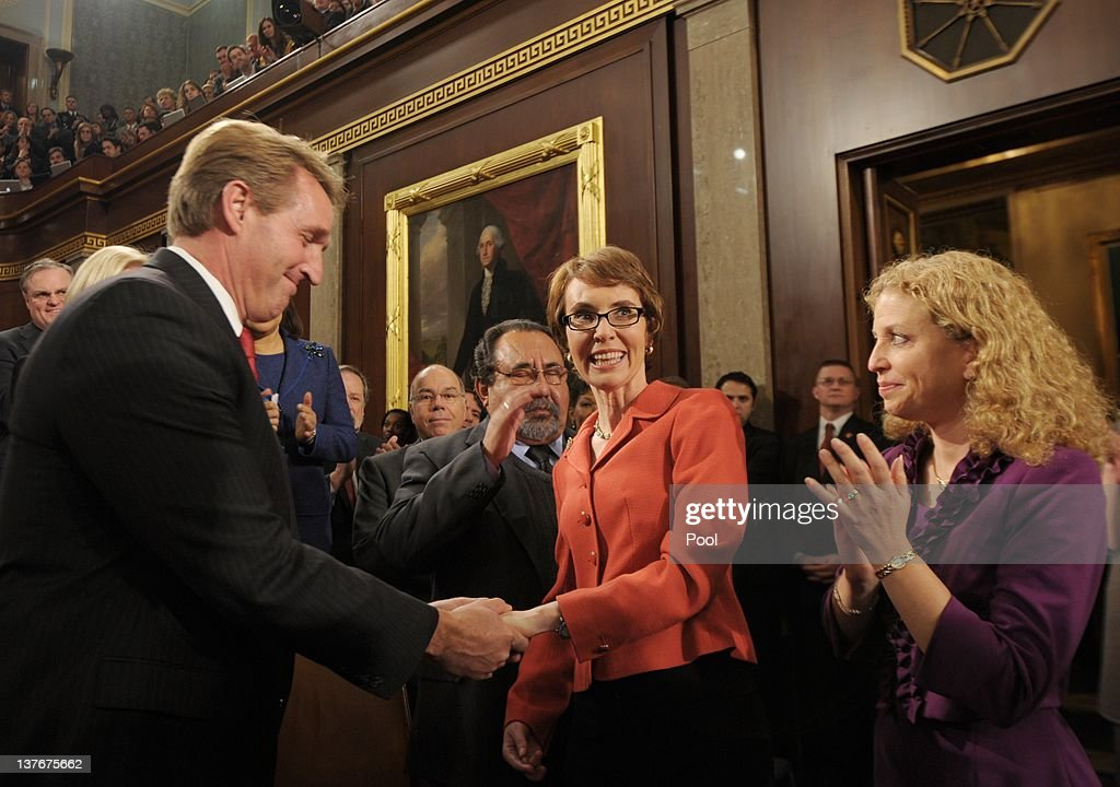 U.S. Rep. <a gi-track='captionPersonalityLinkClicked' href=/galleries/search?phrase=Gabrielle+Giffords&family=editorial&specificpeople=6961081 ng-click='$event.stopPropagation()'>Gabrielle Giffords</a> (D-AZ) (C) is greeted by Rep. <a gi-track='captionPersonalityLinkClicked' href=/galleries/search?phrase=Jeff+Flake&family=editorial&specificpeople=2474871 ng-click='$event.stopPropagation()'>Jeff Flake</a> (R-AZ) and Rep. Debbie Wasserman-Schultz (D-FL) before the State of the Union address before a joint session of Congress on Capitol Hill January 24, 2012 in Washington, DC. The president made a populist pitch to voters for economic fairness, saying the federal government should more do to balance the benefits of a capitalist society.