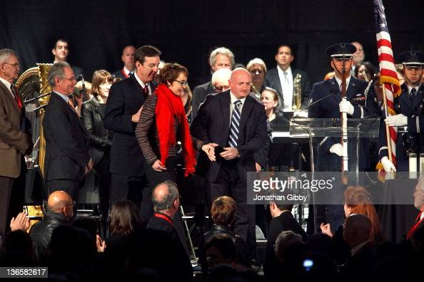S Rep Gabrielle Giffords is helped across the stage by husband Mark Kelly during the 'Remembering January 8th Candlelight Vigil' held at the...