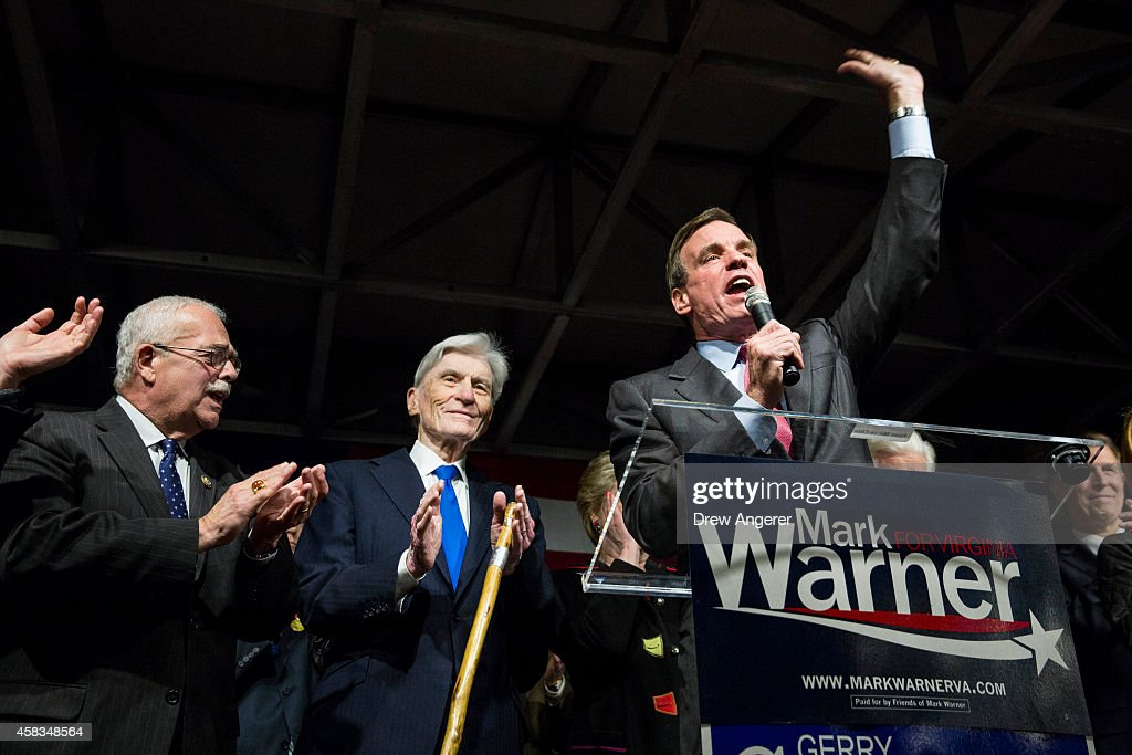 U.S. Rep. Gerry Connolly (D-VA) and former U.S. Senator John Warner (D-VA) look on as Sen. Mark Warner (D-VA) speaks during a Get Out the Vote rally for Democratic candidates, November 3, 2014 in Alexandria, Virginia. Warner, the Democratic incumbent, is running against Republican candidate Ed Gillespie.