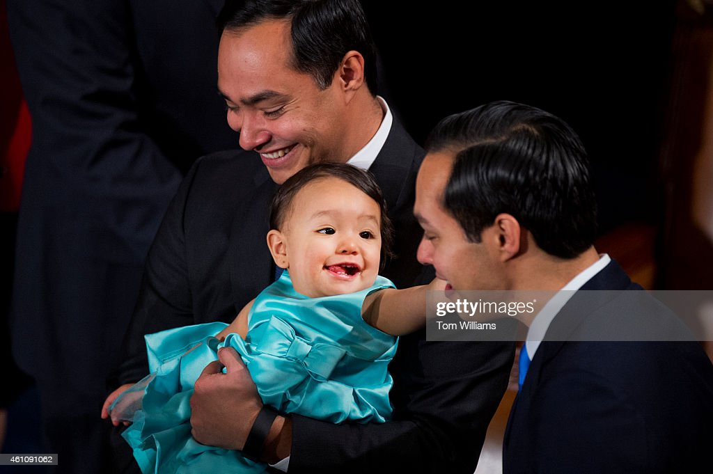Rep. Joaquin Castro, D-Texas, holds his daughter Andrea Elena, as she reaches for her uncle, HUD Secretary <a gi-track='captionPersonalityLinkClicked' href=/galleries/search?phrase=Juli%C3%A1n+Castro&family=editorial&specificpeople=6352991 ng-click='$event.stopPropagation()'>Julián Castro</a>, before the 114th Congress was sworn in on the House floor of the Capitol, January 6, 2015.