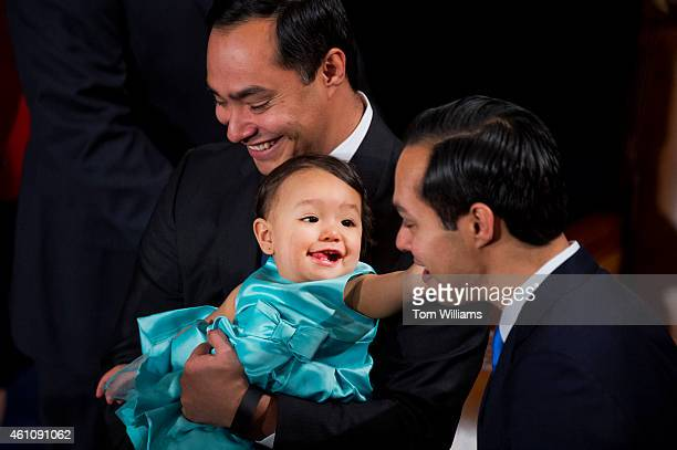 Rep Joaquin Castro DTexas holds his daughter Andrea Elena as she reaches for her uncle HUD Secretary Julián Castro before the 114th Congress was...