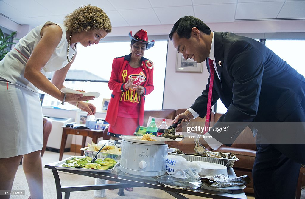 Rep. Joaquin Castro, D-Texas, serves tamales from La Gloria restaurant in San Antonio, to Reps. Frederica Wilson, D-Fla., center, and Debbie Wasserman Schultz, D-Fla., at the DNC. Castro was settling a bet with the Florida members over the NBA finals in which the Miami Heat beat the San Antonio Spurs.