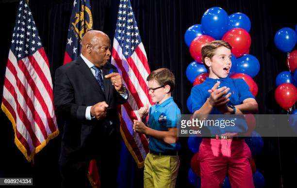 Rep John Lewis DGa dances on stage with two boys before speaking at Jon Ossoff's election night watch party in Atlanta on June 20 2017 Democrat...