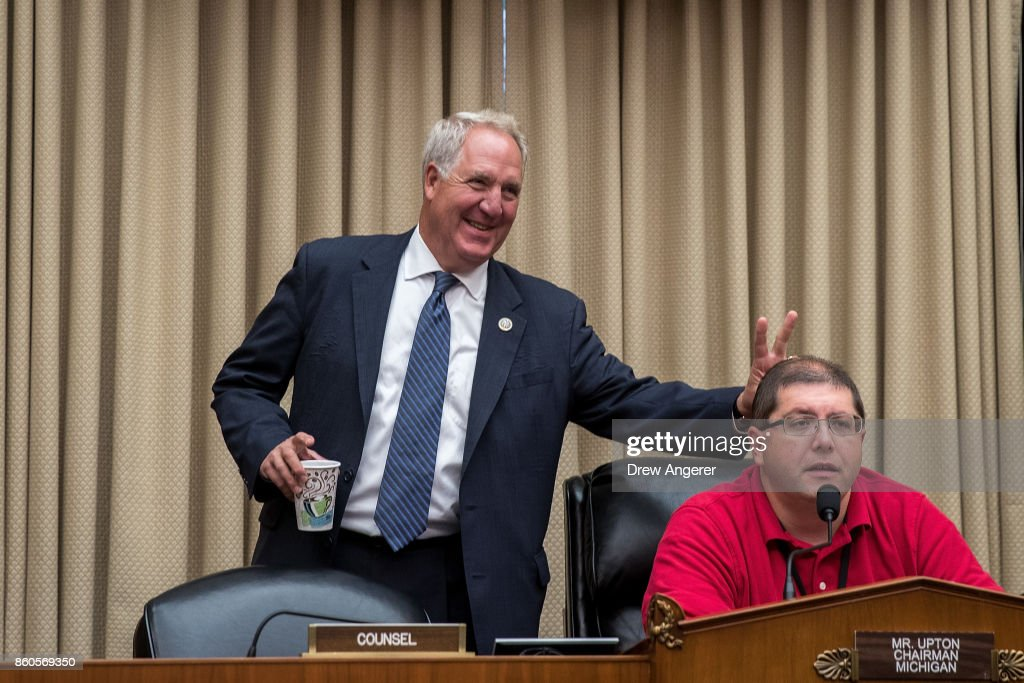 Rep. John Shimkus (R-IL) holds up bunny ear fingers behind a a technician testing the microphones before the start of a House Energy and Commerce Committee hearing on Capitol Hill, October 12, 2017 in Washington, DC. The hearing focused on the U.S. Department of Energy's missions and management priorities.
