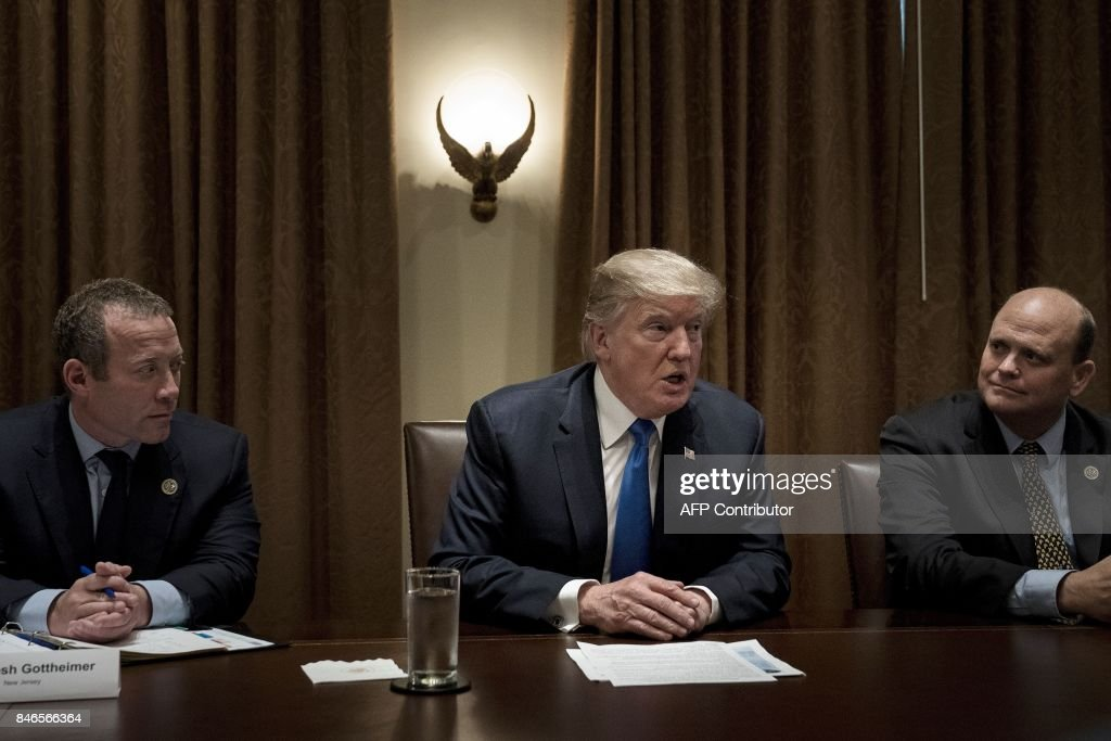 Rep. Josh Gottheimer (Democrat from New Jersey -L) and Rep. Tom Reed (Republican from New York-R) listen while US President Donald Trump addresses a meeting with lawmakers in the Cabinet Room of the White House on September 13, 2017 in Washington, DC. / AFP PHOTO / Brendan Smialowski