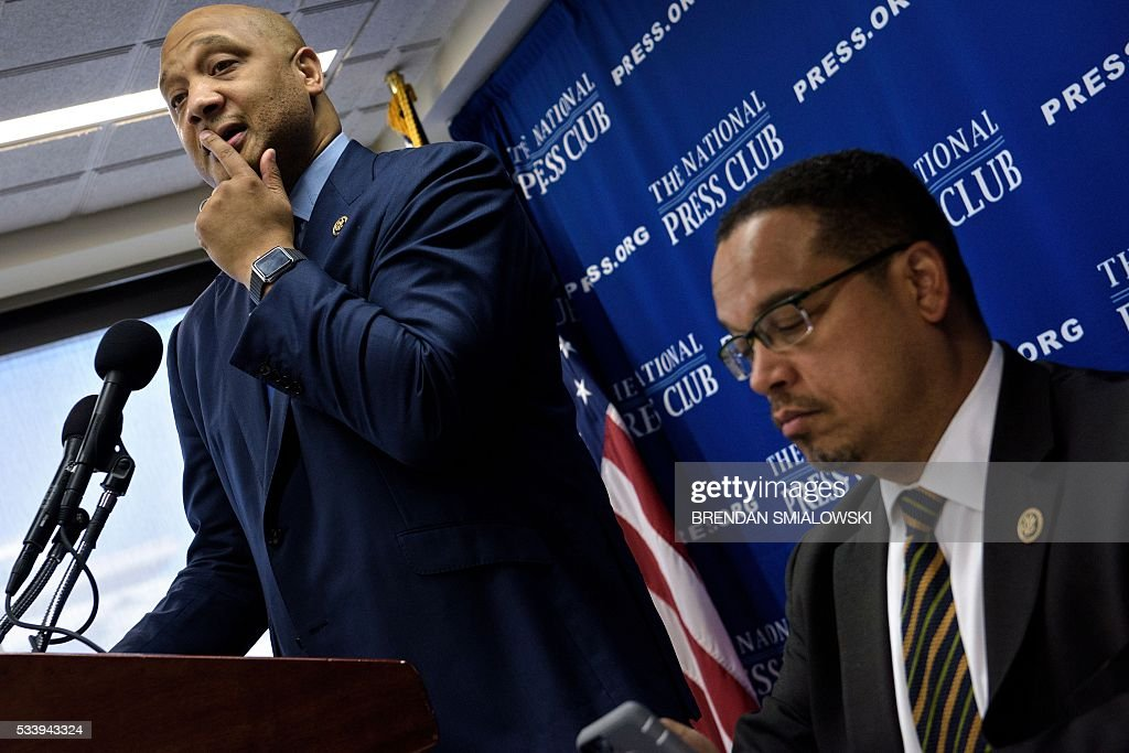 Rep. Keith Ellison(R) D-MN looks at his iPhone while Rep. Andre Carson (D-IN) speaks during a press conference about Islamophobia at the National Press Club May 24, 2016 in Washington, DC. / AFP / Brendan Smialowski