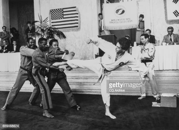 Rep Mel Levine DCalif breaking two boards with wide side kicks while Master Jhoon Rhee a martial arts master watches him on Aug 2 1990 'r'n
