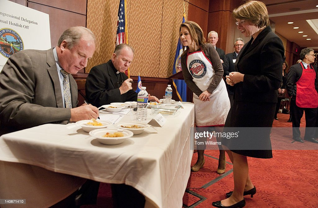 Rep. Michele Bachmann, R-Minn., and Sen. Amy Klobuchar, D-Minn., right, check on judges former Rep. Vin Weber, R-Minn., left, and House Chaplain Patrick Conroy during the second annual 'hotdish' competition in the Capitol Visitor Center, featuring casserole-like dishes from members of the Minnesota Congressional Delegation. The dishes of Sen. Al Franken, D-Minn., and Rep. Chip Cravaack, R-Minn., tied for first place in the competition.