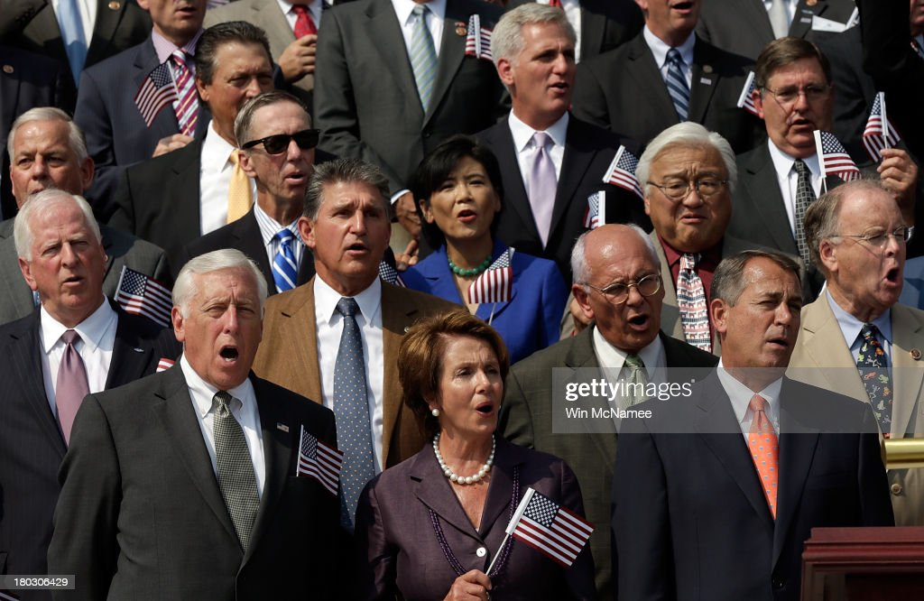 Rep. Steny Hoyer (D-MD), House Minority Leader Nancy Pelosi (D-CA), and Speaker of the House John Boehner (R-OH) wave American flags along with other members of Congress as they sing 'God Bless America' during a September 11th remembrance ceremony on the steps of the U.S. Capitol September 11, 2013 in Washington, DC. The nation is commemorating the anniversary of the 2001 attacks which resulted in the deaths of nearly 3,000 people after two hijacked planes crashed into the World Trade Center, one into the Pentagon in Arlington, Virginia and one crash landed in Shanksville, Pennsylvania.