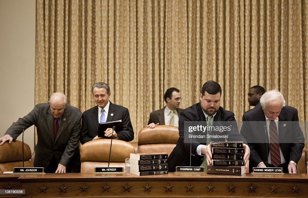 Rep. Timothy V. Johnson (R-IL) (L), Rep. Wally Herger (R-CA) (2L) and Committee ranking member Rep. Sander Levin (D-MI) (R) take their seats as a staff member stacks tax code books before the start of the 112th Congress's first hearing of the House Ways and Means Committee on Capitol Hill January 20, 2011 in Washington, DC. The Committee called business and tax leaders to testify about the effect of the Federal income tax on tax payers and the economy.