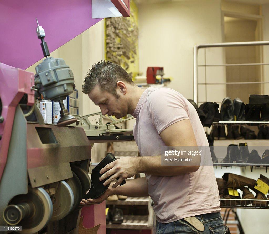 Repair man polishes shoe