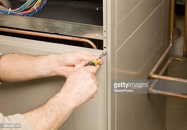Repair Technician Removing Furnace Service Panel