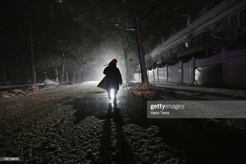 A repair worker is silhouetted by a police spotlight as he walks down a darkened street during a Nor'Easter snowstorm on November 7, 2012 in the Rockaway neighborhood of the Queens borough of New York City. The Rockaway Peninsula was especially hard hit by Superstorm Sandy and some are evacuating ahead of the coming storm.