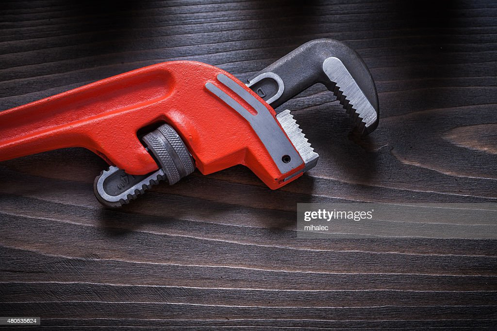 Repairing adjustable wrench on flat brown vintage board construc : Stock Photo