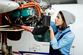 Young woman in uniform fixing something in air jet motor