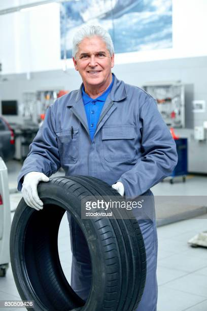 Repairman and black rubber tire in the service