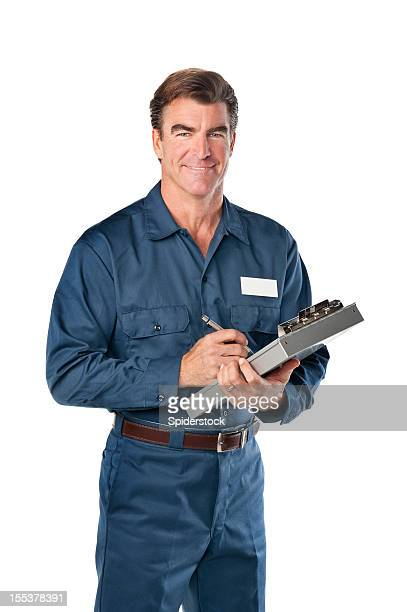Repairman in blue uniform with clipboard