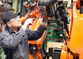 Mechanic repairing a robot machine