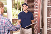 Latin descent blue collar/service industry worker or delivery person makes service/house call at customer's front door.  He holds a clipboard while shaking hands with customer.  The man wears a blue u