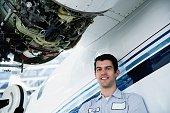 Repairman smiling next to airplane engine