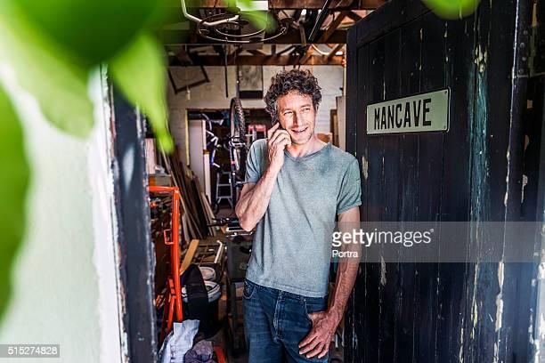Repairman using mobile phone at doorway