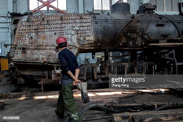 A repairman walks by an old steam locomotive in the maintenance factory There are less and less steam trains to be repaired and the factory will be...