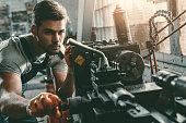 young handsome repairman working in repair shop