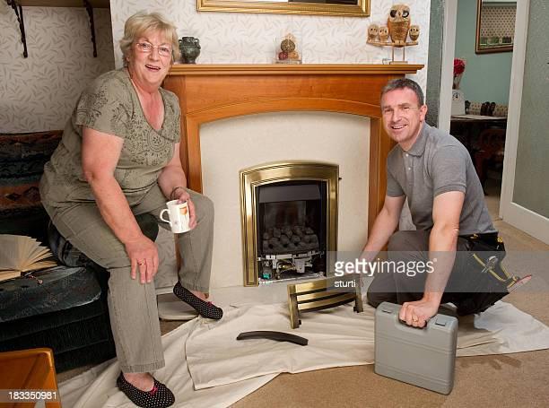 Réparateur travaillant sur une cheminée pour une femme âgée