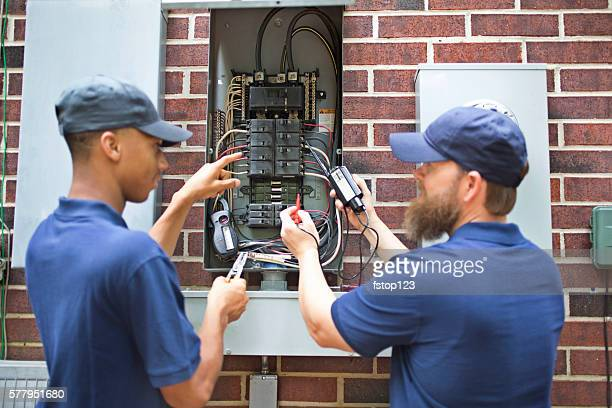 Repairmen, electricians working on home breaker box.