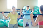 Two happy oversized women with gymnastic bars doing exercises after their instructor in gym