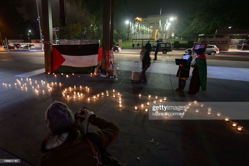REPEAT---Pro-Palestinian demonstrators stand next to candles during a protest against the Israeli offensive in Gaza on November 21, 2012 in front of the United Nations Office in Geneva. A ceasefire agreed between Israel and Hamas officially came into effect on the basis of the text of the deal announced shortly beforehand in Egypt. AFP PHOTO / FABRICE COFFRINI