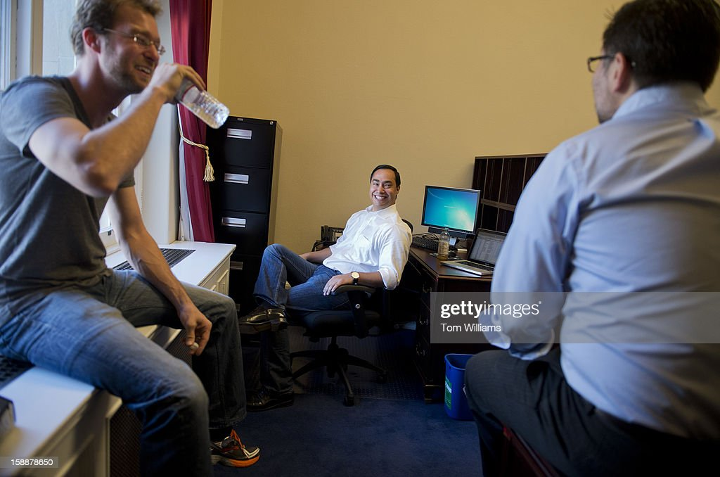 Rep.-elect Joaquin Castro, D-Texas, center, shares a laugh with aides Matthew Jones, left, and Carlos Sanchez, during a break in arranging his Cannon Building office.