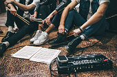 Repetition of rock music band. Cropped image of guitar players and drummer are sitting on the floor at rehearsal base with notes.