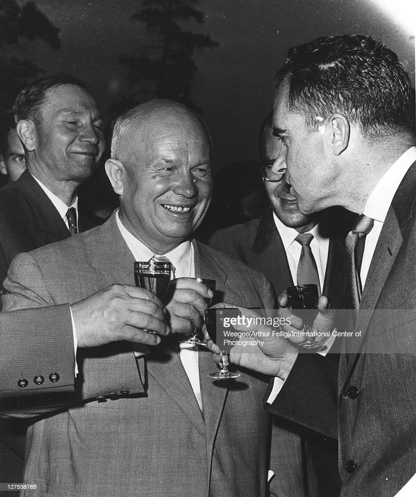 Re-photographed image of Russian politician and Soviet Premier Nikita Khrushchev (1894 - 1971) (center) as he smiles and shares a toast with American politician US Vice President (and future US President) Richard Nixon (1913 - 1994), late 1950s. (Photo by Weegee(Arthur Fellig)/International Center of Photography/Getty Images)