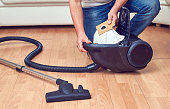 Man taking out a full dust bag from a vacuum cleaner